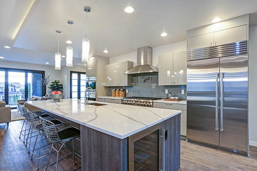 Kitchen with modern white high gloss cabinets silver hardware long calacatta countertop island wood flooring