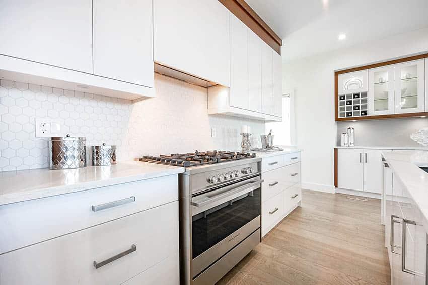 Kitchen with white lacquer cabinets white quartz hexagon shaped tile backsplash wood flooring