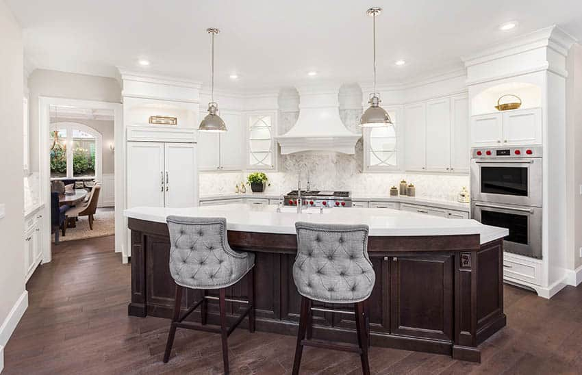 Kitchen with white solid surface corian countertops with raised breakfast bar island white cabinets