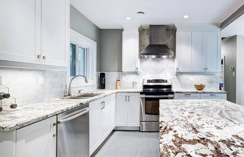 L shaped kitchen with granite countertops island and white cabinets