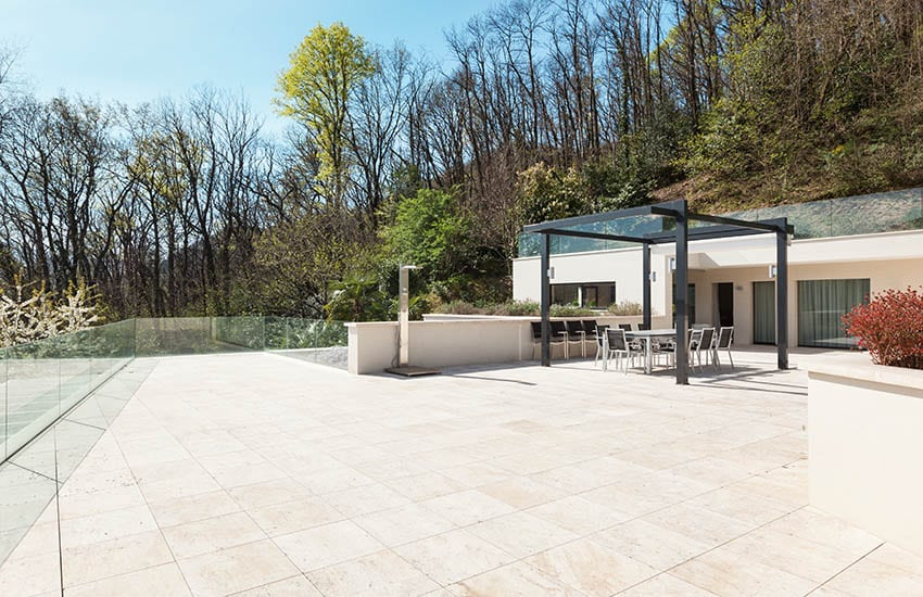 Large travertine paver patio with modern pergola with glass ceiling