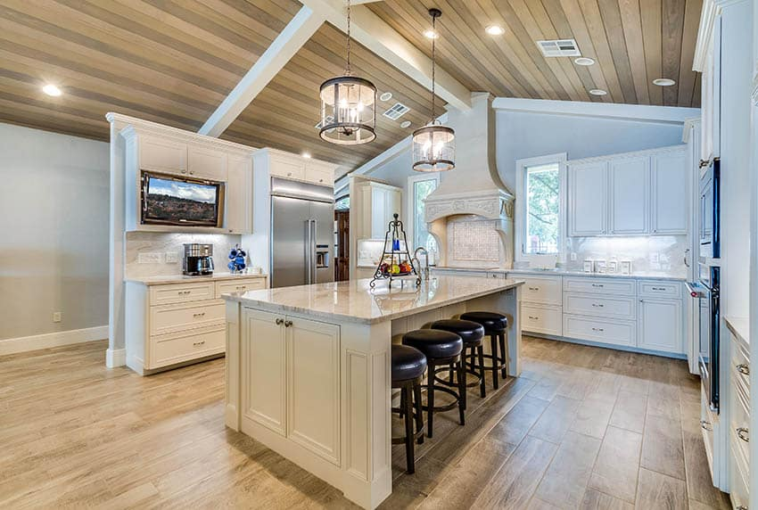 Large u shaped kitchen with light color dekton countertops cream cabinets wood plank arched ceiling