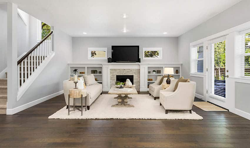Living room with white shag wool rug stacked stone fireplace built in bookshelves wood flooring