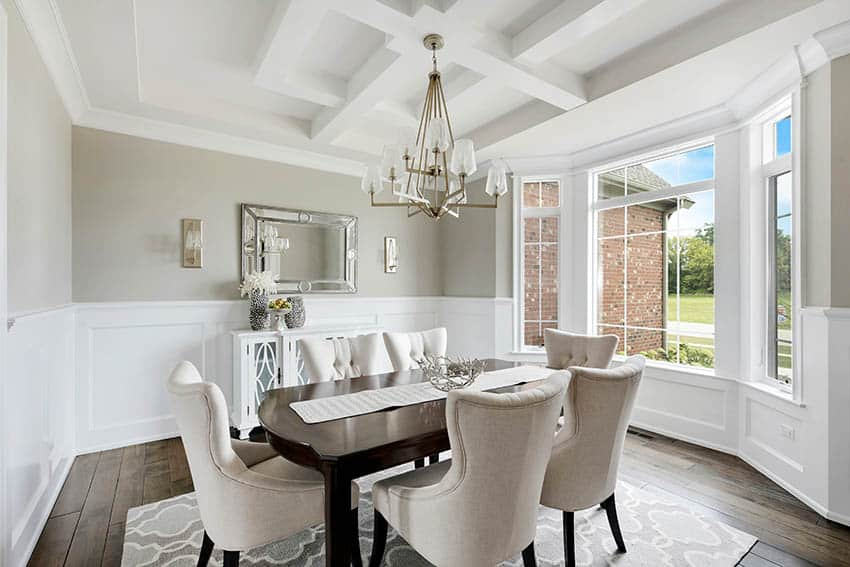 Luxury dining room with board and batten wainscoting beige wall paint chandelier