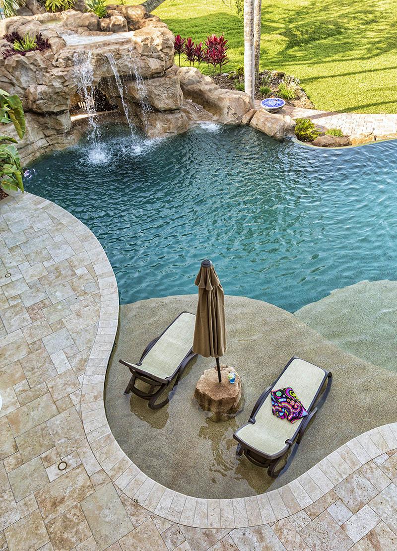 Luxury lagoon swimming pool with travertine deck sun shelf lounge chairs rock waterfall