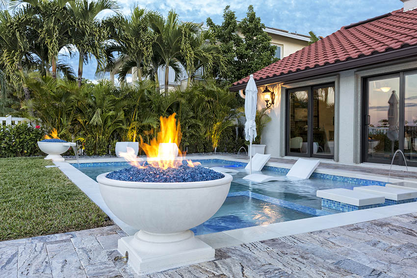 Marble swimming pool deck with fire pit pots tropical landscape