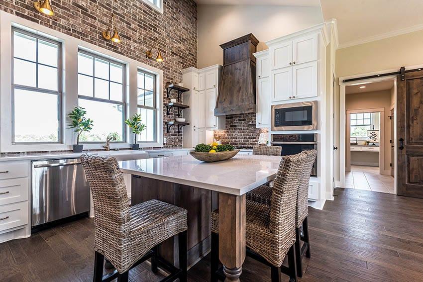 Modern farmhouse kitchen with dekton countertops white cabinets wood island brick wall wood oven hood