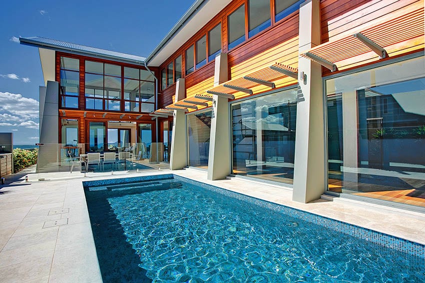 Modern home with large travertine pool deck