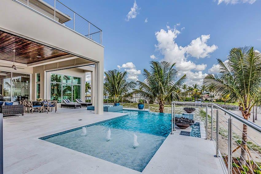 Modern infinity edge pool with white travertine deck
