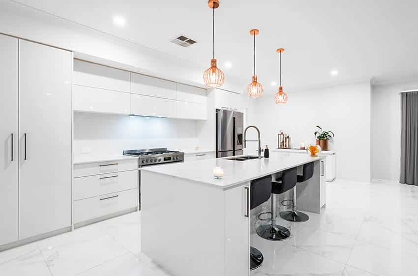 Modern kitchen with white high gloss cabinets large island with white quartz marble look porcelain tile flooring
