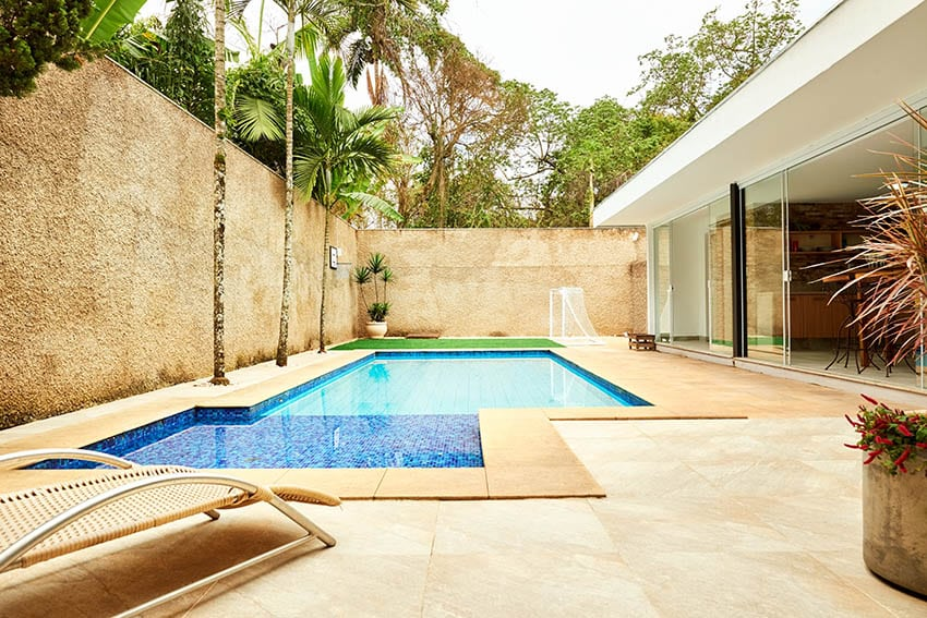 Modern swimming pool with large travertine paver deck palm trees high privacy wall
