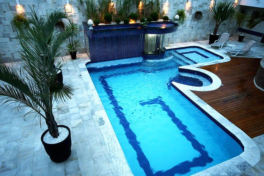 Piscina moderna con terraza de mármol y terraza de madera.