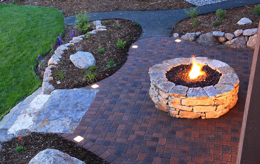 Patio with sealed brick pavers stone fire pit rock grass mulch landscaping