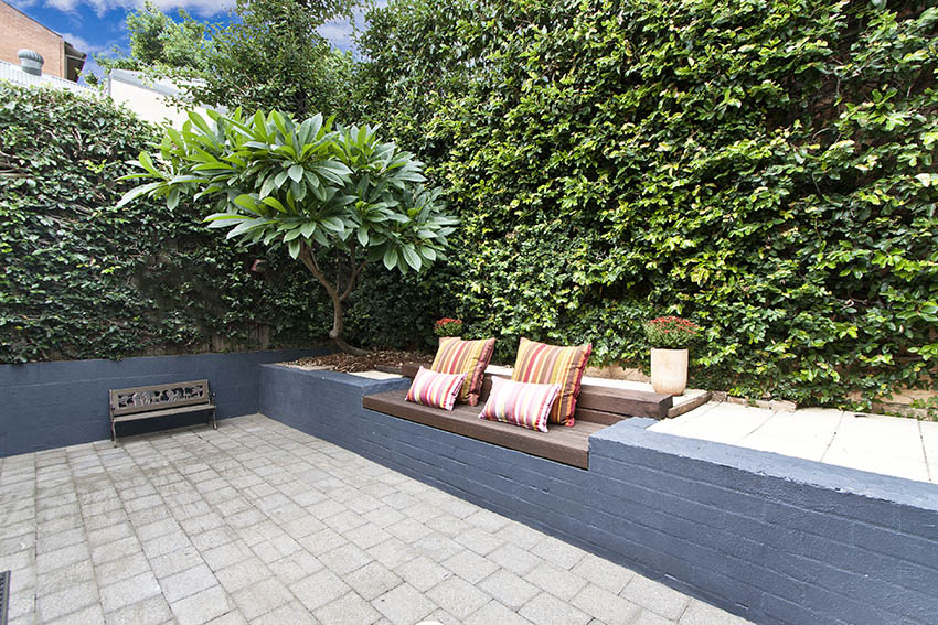 Paver patio with natural wind blocking bushes and built in bench seat