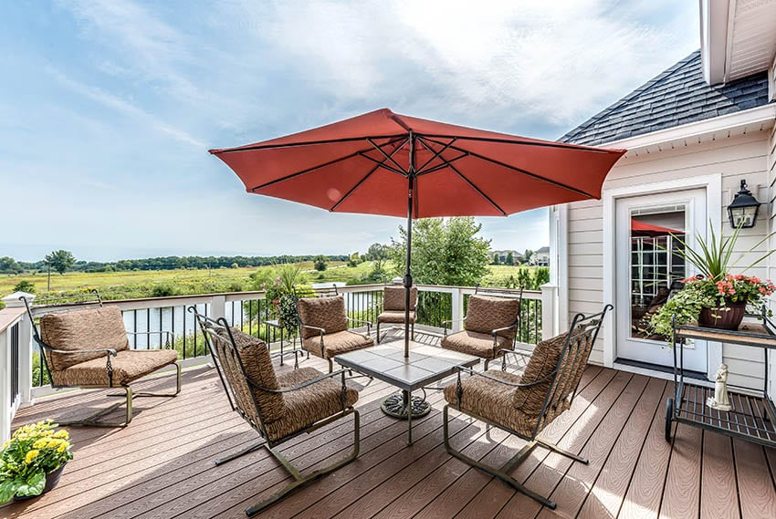 Raised azek deck with white railing outdoor dining waterfront views