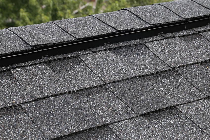 Roof ridge vent cap with dark shingles