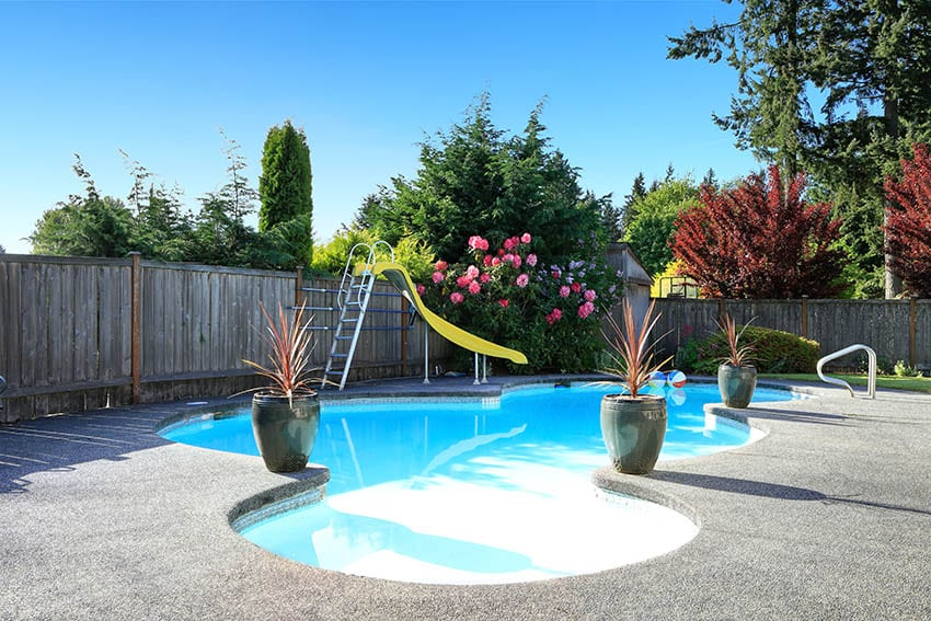 Swimming pool with exposed aggregate deck curved design slide