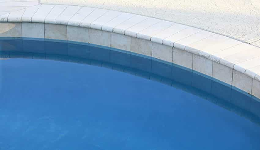 Swimming pool with limestone cantilever pool deck coping