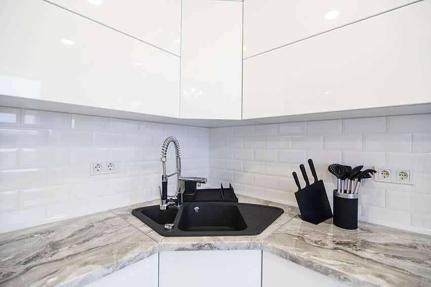 White lacquer kitchen cabinets with black synthetic granite corner sink