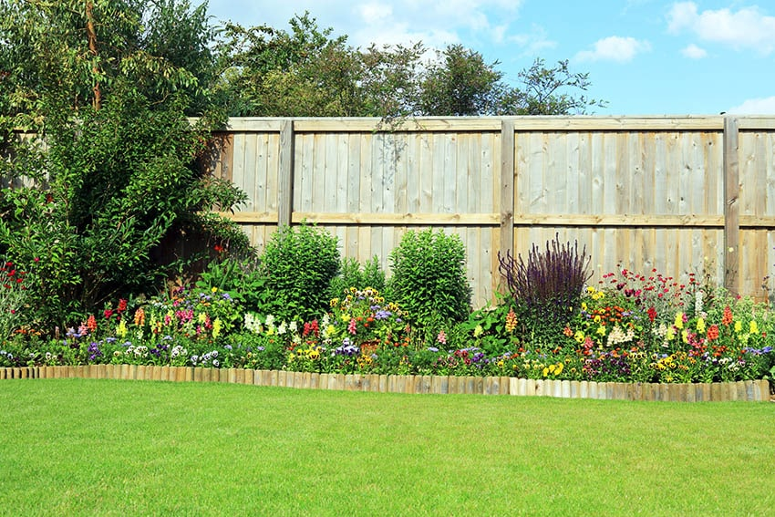 Wooden garden edging with flowering plants and large wood backyard fence