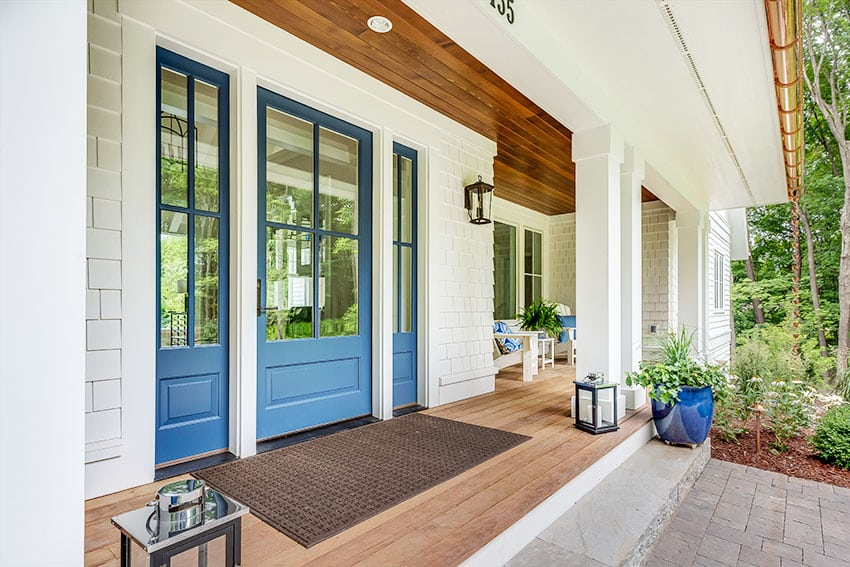 Blue front door with shingles walling and horizontal wooden ceiling