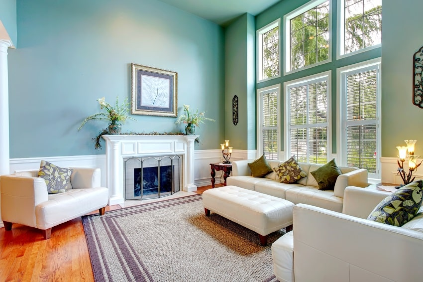 high ceiling aqua sunroom color with white leather couch ottaman armchairs and fireplace