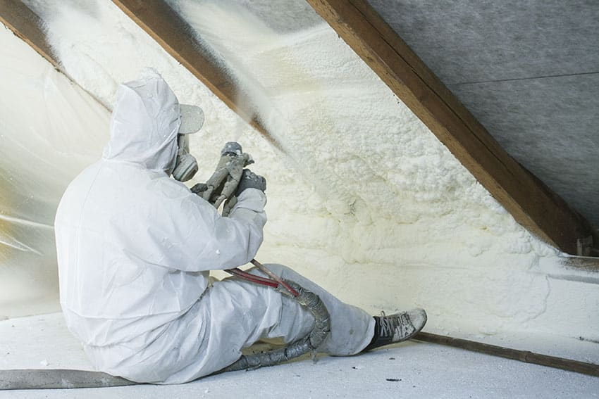 Man spraying foam insulation in roof rafters