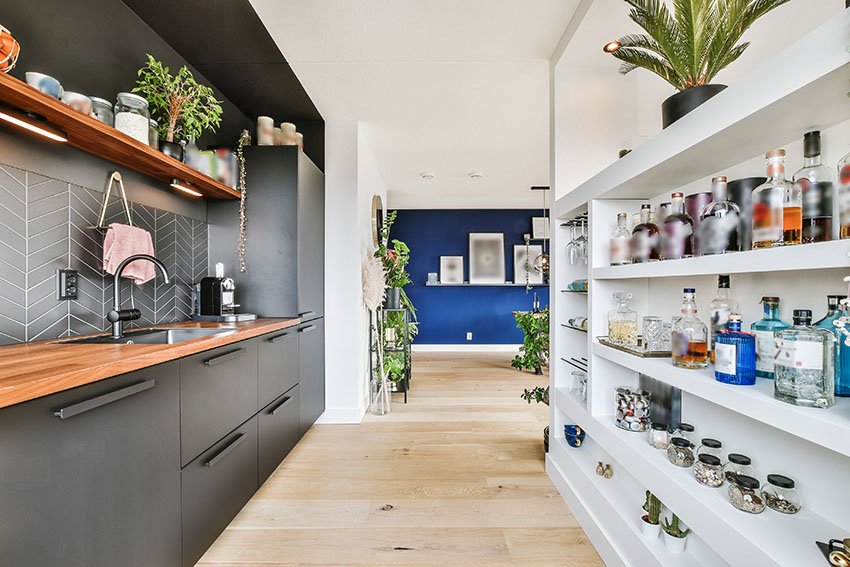 Modern kitchen with wooden countertop black cabinets white pantry