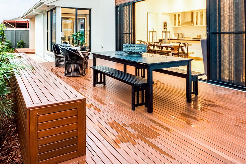 Patio with black polymer dining table and red wood floor