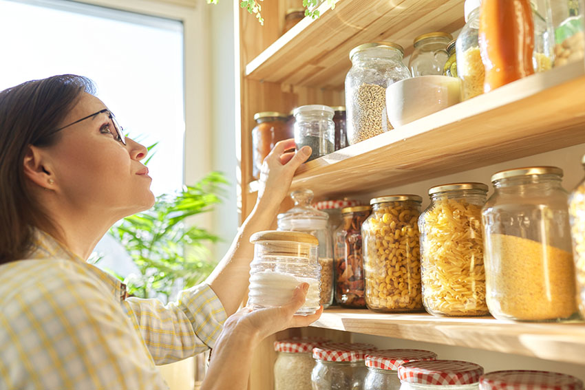 Woman picking bottled herbs and spices in pantry