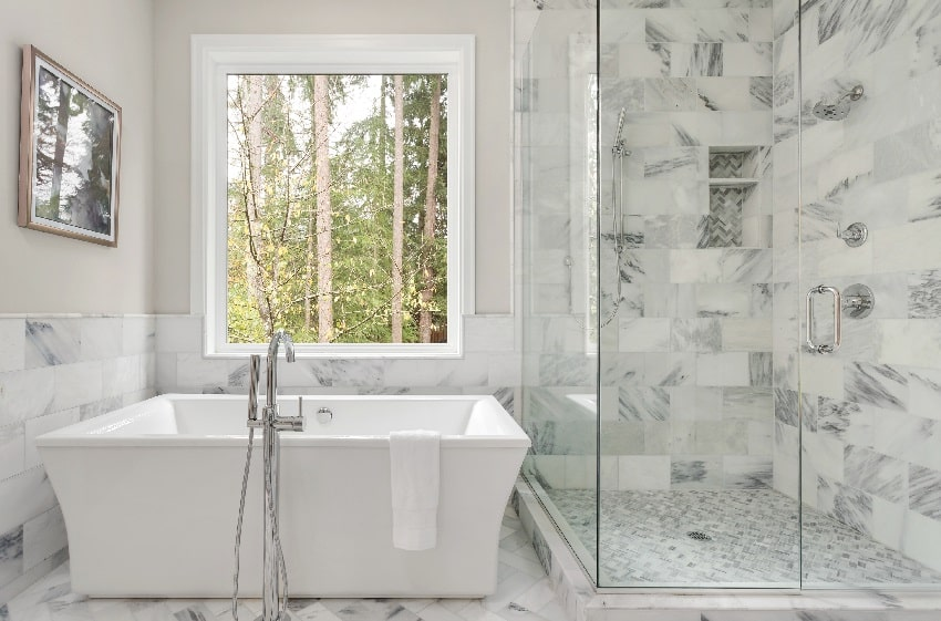 bathroom interior with large shower elegant tile and soaking bathtub large window with view of trees