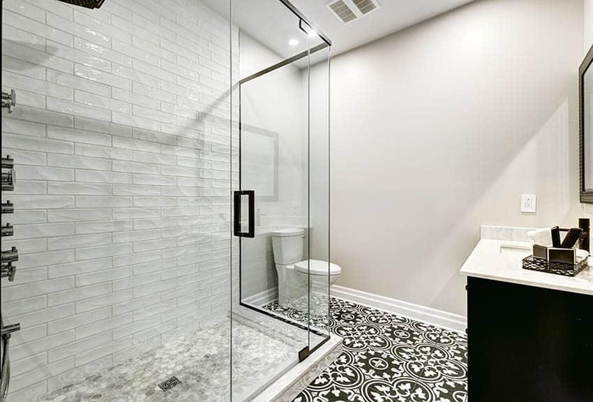 Bathroom shower with porcelain mosaic tile floor and black white spanish style tile floor