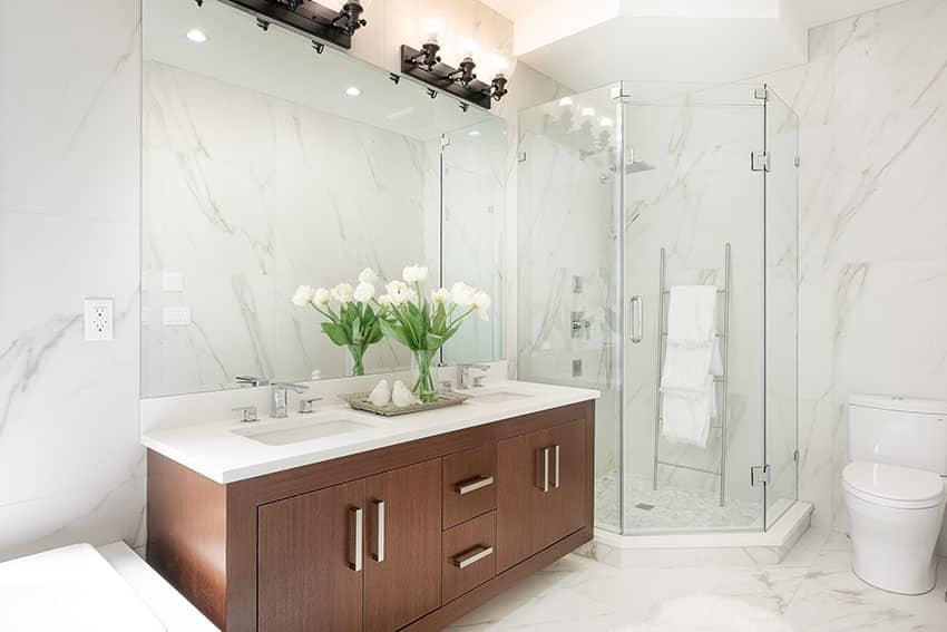 Baño con puerta de ducha sin marco y mueble marrón