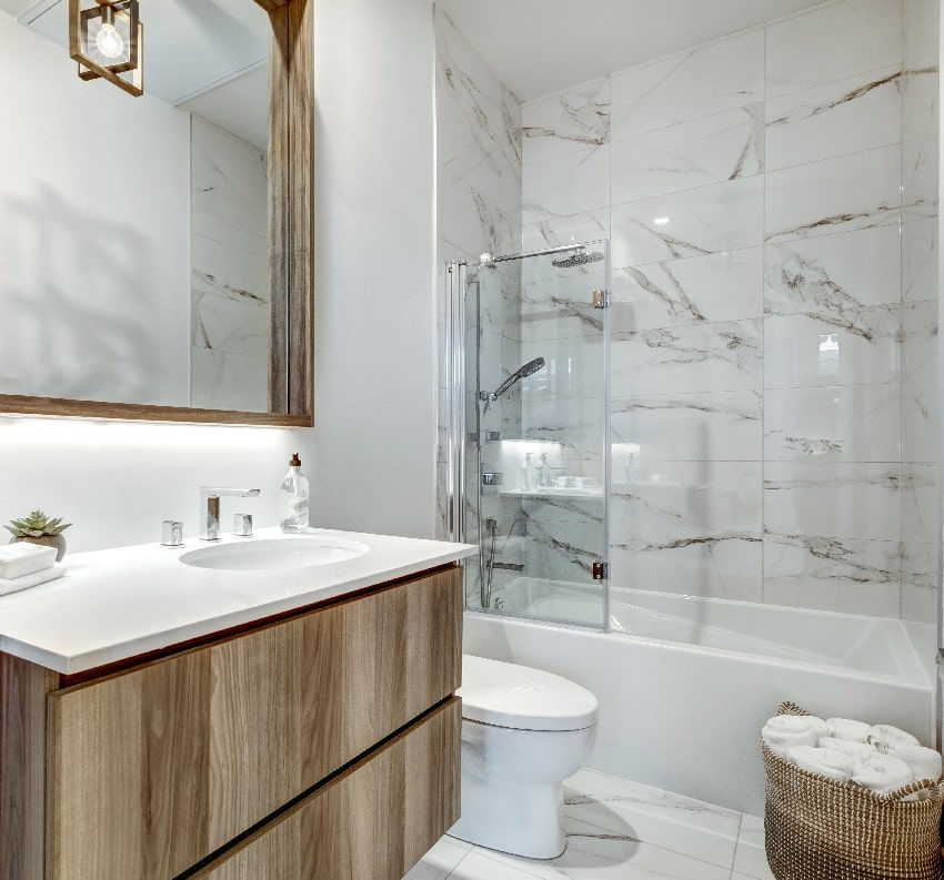 bathroom with marble shower tile mirror basket with towels and wooden cabinets