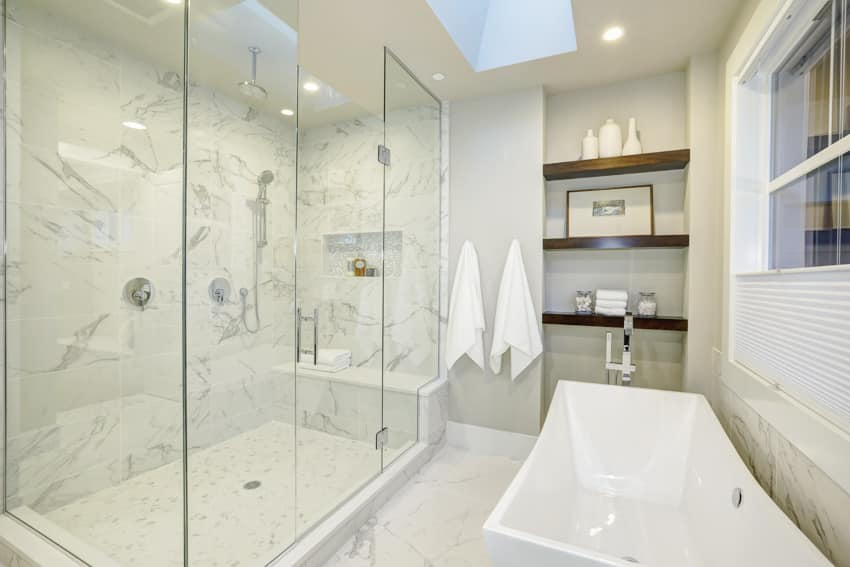 Bathroom with porcelain bathtub glass built in shower bench and wooden shelves