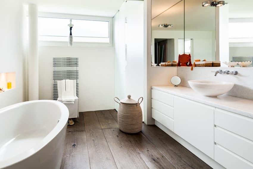 Bathroom with wood flooring bathtub and oval sink