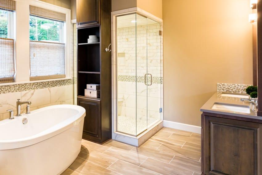 Bathroom with wood flooring glass door and bathtub