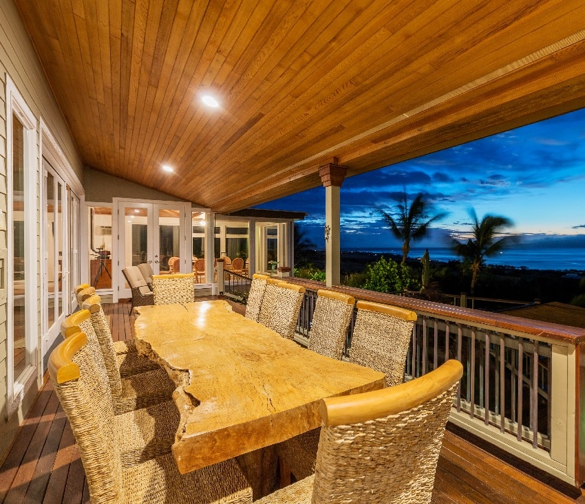 beautiful home exterior patio deck and dining table with recessed lighting and sunset view