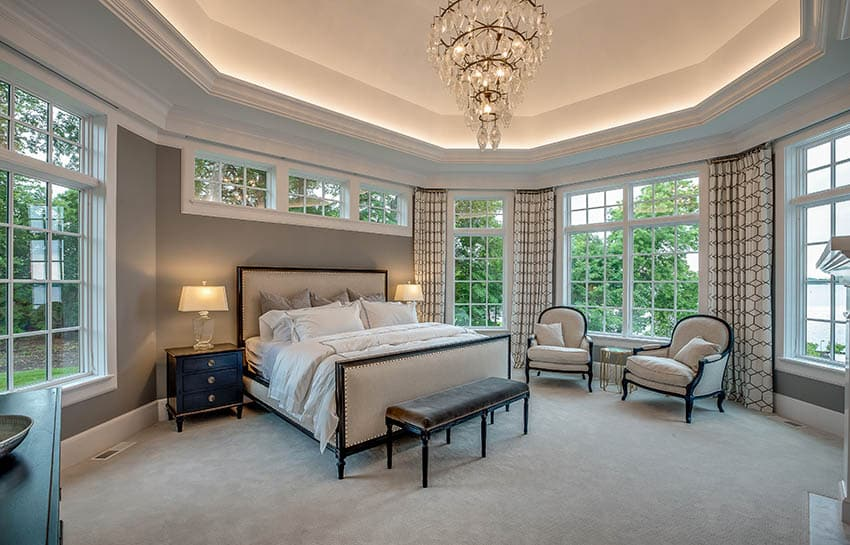 Beautiful master bedroom with lighted geometric tray ceiling with chandelier