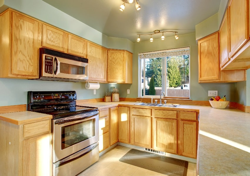 beautiful traditional kitchen with hardwood floor oak wood cabinets light green wall stove and oven