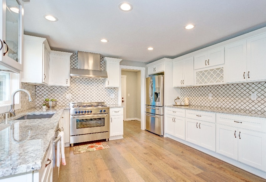beautiful white kitchen room with moroccan tiles, white ceiling paint finish and modern stainless steel appliances