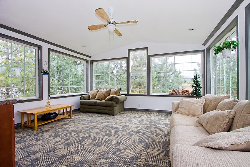 big sunroom in a house with ceiling fan sofa and plants