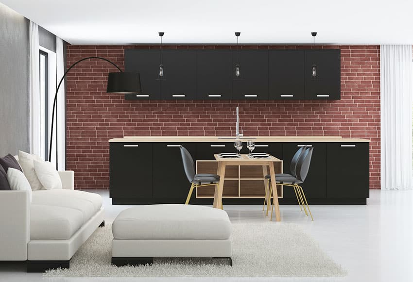 Black kitchen cabinet with red brick wall