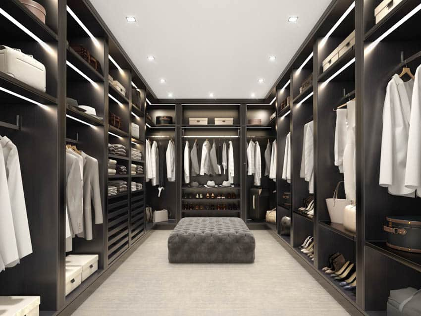 Black walk in closet with tufted ottoman