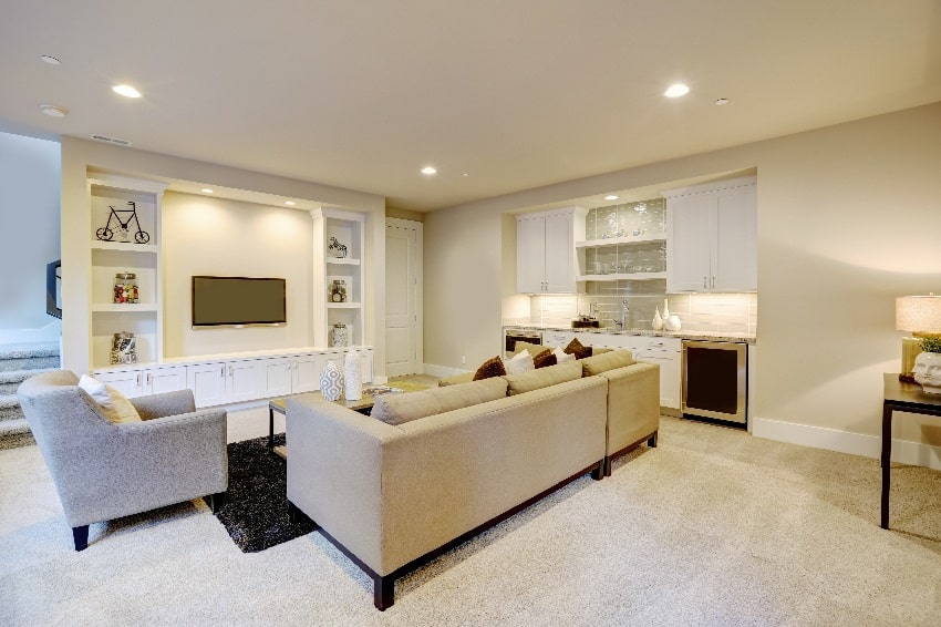 chic basement features a light brown sectional facing white wall with built in tv and cabinets