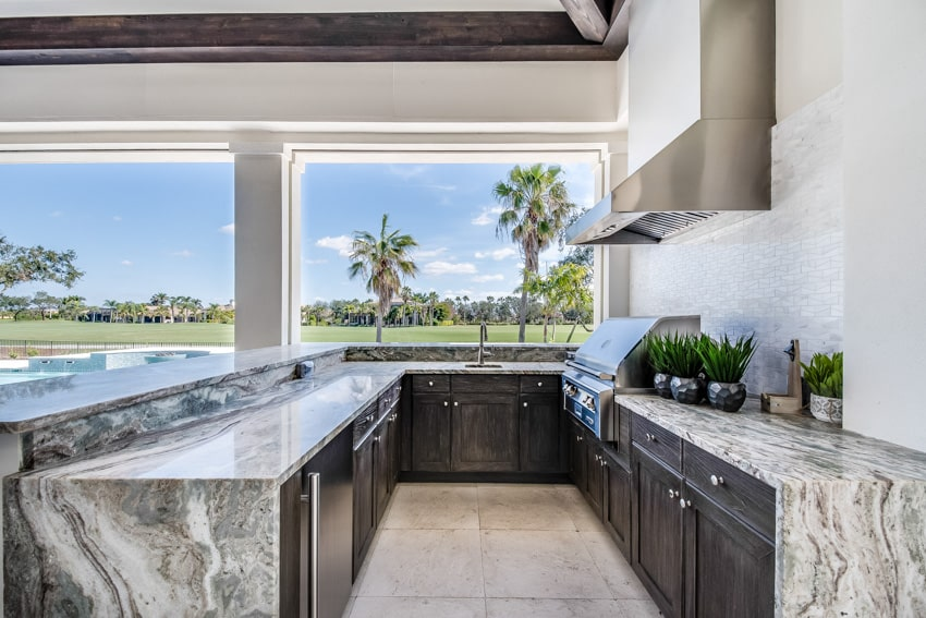 Classy looking outdoor kitchen with grill hood cabinets countertop and island