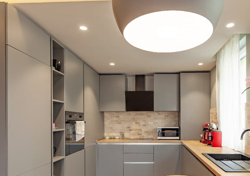 closed kitchen design with grey cabinets and matte finish ceiling
