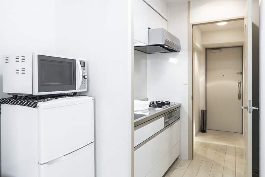 Compact kitchen with stove against wall