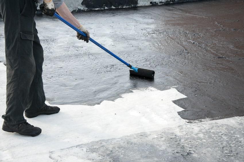 Construction worker using bituminous primer for waterproofing