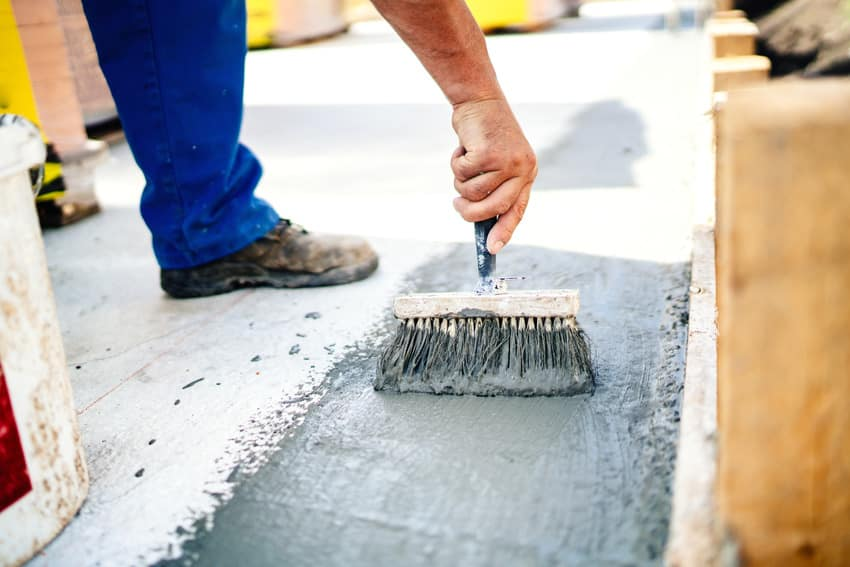 Construction worker using cementitious waterproofing